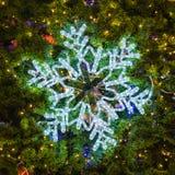 Lumière de flocon de neige et ornement décoratif sur l'arbre de Noël Photographie stock libre de droits