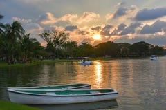 Lumière de Sun de soirée et bateau de rangée en parc Thaïlande de lac Photo stock