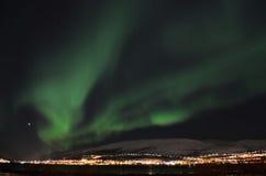 Lumière du nord puissante dansant au-dessus de la crête de montagne neigeuse en Norvège du nord sur le règlement d'île de baleine Image libre de droits