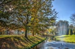 Lumière du soleil, arbres, étang et fontaine photographie stock libre de droits