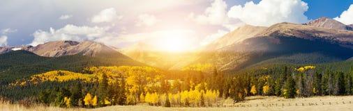 Lumière du soleil brillant au-dessus des crêtes de haute montagne et des arbres d'or de tremble dans un paysage panoramique du Co image libre de droits