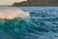 Lumière du soleil d'aube éclairant une vague à contre-jour de rupture photo stock