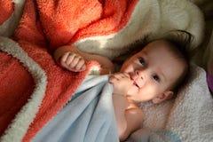 Lumière du soleil de matin caressant un bébé garçon photos stock