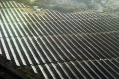 Lumière du soleil de visage de panneaux solaires sur le champ vert Photographie stock libre de droits