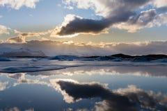 Lumière du soleil derrière le nuage blanc au-dessus de la lagune de saison d'hiver de Jakulsarlon Image stock