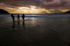Lumière du soleil sous une pluie de nuage avant coucher du soleil sur la mer, personnes de silhouette Images stock