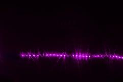 Lumière laser pourpre rougeoyant dans l'obscurité dans le mur de boîte de nuit Image stock