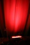 Lumière rouge d'endroit contre le rideau Photographie stock libre de droits