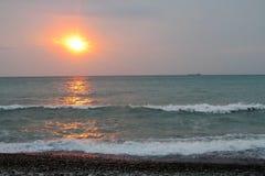 Lumière rouge de coucher du soleil au-dessus de la mer, silhouette de bateau Photos stock