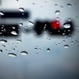 Lumière rouge par la fenêtre en pleuvant le jour Photographie stock libre de droits