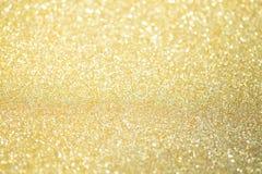 Lumières abstraites de bokeh de scintillement d'or avec le fond clair mou photos stock