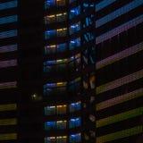 Lumières colorées de fenêtres de nuit du bâtiment résidentiel ayant beaucoup d'étages dans le secteur de sommeil de ville Photo stock