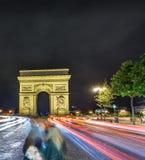 Lumières d'Arc de Triomphe et de voiture la nuit Image stock