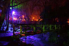 Lumières de conte de fées et pont en bois en parc Image stock