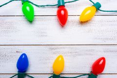Lumières de Noël colorées sur un fond en bois blanc de lamelle images libres de droits
