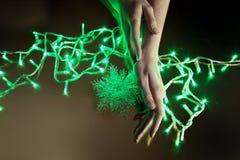 Lumières de Noël dans des mains d'une beauté Photographie stock libre de droits
