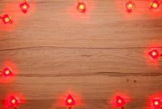Lumières de Noël en forme de coeur sur le bois Image stock