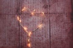 Lumières de Noël de forme de coeur sur le fond rustique Image libre de droits