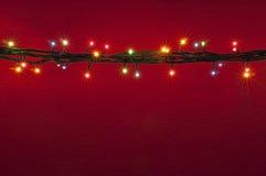 Lumières de Noël sur le fond rouge Fond multicolore de rouge de lighton Photo stock