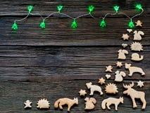 Lumières de Noël sur un fond en bois avec l'espace libre Pain d'épice sous forme d'animaux, étoiles et coeurs Photographie stock libre de droits