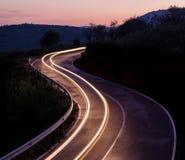 Lumières de voiture dans le coucher du soleil Photographie stock libre de droits