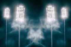 Lumières et fumée de stade contre le ciel nocturne foncé Photographie stock