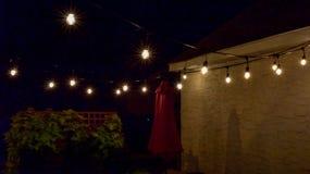 Lumières extérieures accrochantes au-dessus de patio dans la nuit d'été photos stock