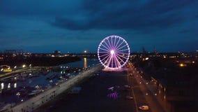Lumières gauches rougeoyantes de grues et de roue de ferris le soir sur les boulevards 4K clips vidéos