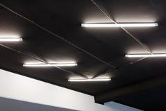 Lumières menées de tube sur le plafond noir de bureau Conception minimale de grenier photos libres de droits