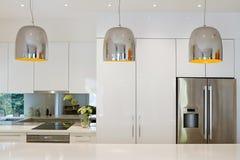Lumières pendantes contemporaines accrochant au-dessus de l'île de cuisine Photo libre de droits