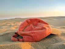 lumi?re de coucher du soleil d'un chapeau rouge abandonn? ou oubli? sur le sable brun de la dune du d?sert par une personne de to image libre de droits