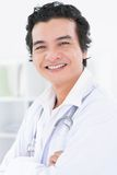 Luminary of medicine. Vertical portrait of a happy handsome physician being friendly and self-confident Royalty Free Stock Images