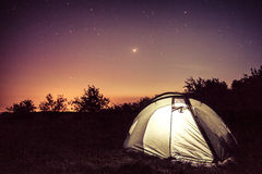 Luminescence in a tent under stars. Bright tent under the stars in the mountains Royalty Free Stock Photography