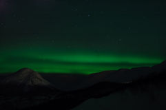 Luminescences of Aurora polaris. Above a mountain valley Royalty Free Stock Images