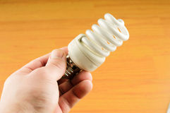 Luminescent light bulb in his hand Royalty Free Stock Image