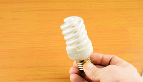 Luminescent light bulb in his hand Royalty Free Stock Photography