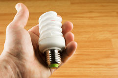 Luminescent light bulb in his hand Royalty Free Stock Photos