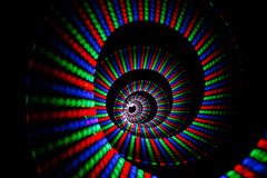 Luminous colors of rainbow trail in form of spiral. On black background. Isolated stock illustration