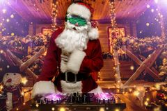 Luminous glasses and headphones. DJ Santa Claus in luminous glasses and headphones holds a party near his house decorated with lights. Christmas songs and music stock images