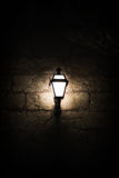 A luminous lantern. On a stone wall Royalty Free Stock Images