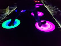 Luminous LED circles that illuminate when stepped on in different colors. Red parple blue white brown orange purple green yellow shoes people fun funny standing royalty free stock photography