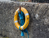 A luminous life saving ring and buoyancy hangs on the harbor wall in Ballintoy on the North Coast of Ireland. These and other devices provide vital lifesaving Royalty Free Stock Image