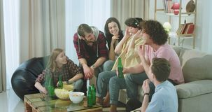 In a luminous living room group of multi ethnic friends very attractive have a good time together drinking beer one of stock video