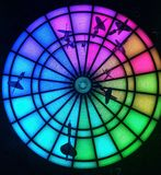 Luminous multicolored dartboard with several darts stuck royalty free stock photography