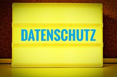 Luminous panel with the inscription in German Datenschutz in front of a pin board, in English Privacy Policy, in yellow with light. Blue letters stock image