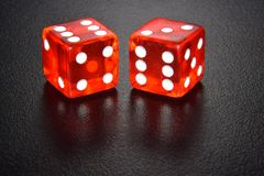Two red luminescent casino dice on black reflecting background royalty free stock image