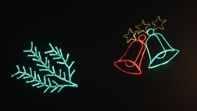 The glowing bells blink against a dark background. Christmas decorations, festive lighting. Luminous red and green bells and spruce twig blink against a dark stock video