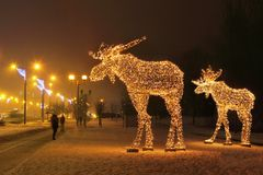 Two Luminous Moose. Luminous two moose come out of the forest in the evening city. Belarus, Minsk, Europe stock photography