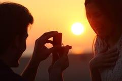 Lumière arrière d'une proposition de mariage au coucher du soleil Image libre de droits