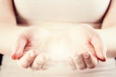 Lumière chez des mains de la femme Donner, se protègent, s'inquiètent, énergie Photo stock